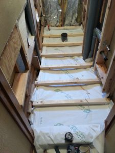 床下断熱材を敷く準備をします。断熱材を下から支えるための防湿シートを敷きます。