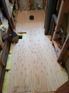 床下に黄色の断熱材を入れ、合板下地を敷きます。